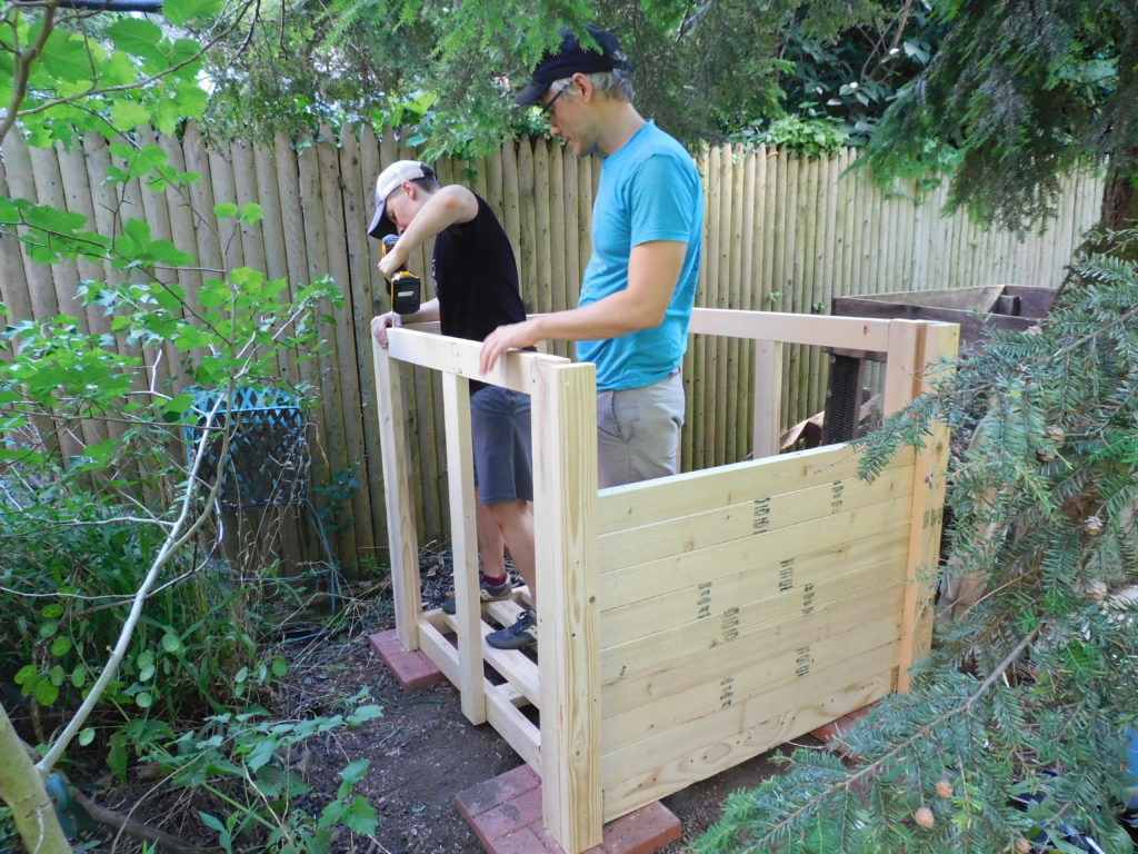 Two gardeners constructing a wooden compost bin