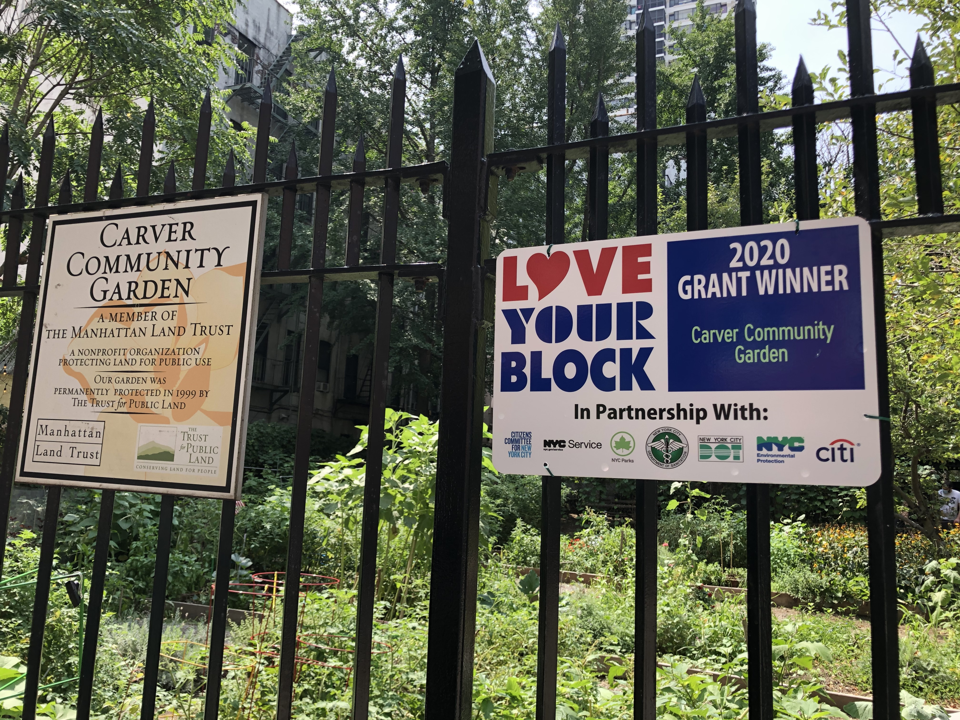a love your block grant sign hanging outside carver community garden